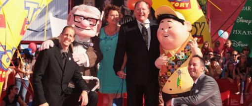 """Peter Docter (t.v.) and John Lasseter (tredje høyre) poserer med """"Se opp""""-karakterene Carl Fredricksen og Russell under årets filmfestival i Venezia"""