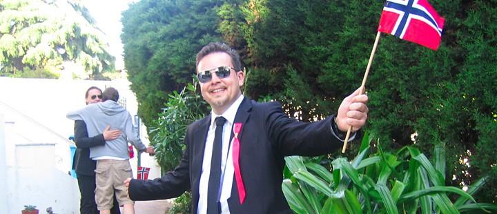 17. mai: Filmprodusent Eric Vogel i et nasjonalromantisk øyeblikk under årets Cannes-festival. I bakgrunnen klemmer skuespiller Mads Ousdal (aka. Arne Treholt, ninja) og Geir Lian, filmsjef i Euforia. (Foto: Klaus Sandvik)