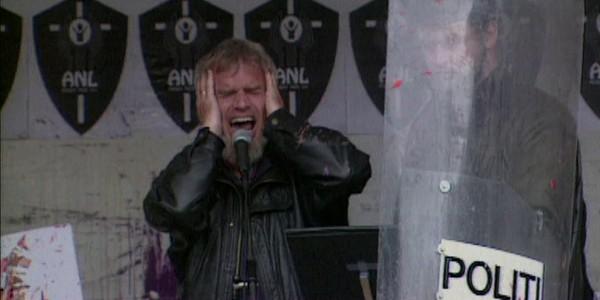 Børre Knudsen simulerer et ufødt barns skrik. Illsinte påhørere blir holdt tilbake av politiet.