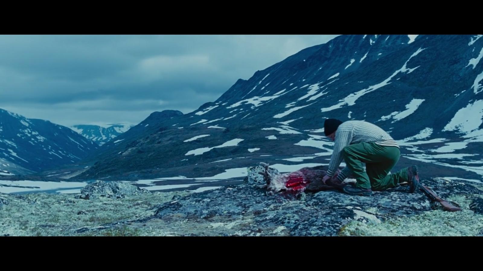 ...og seiler forbi faren som slakter et reinsdyr...