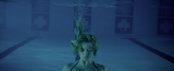Kameraet følger Jay ned i vannet som en elevator, og rapporterer omsorgsfullt om elegante bevegelser i hår og armer. Lilla fargetoner gjør seg gjeldende også i vannet.